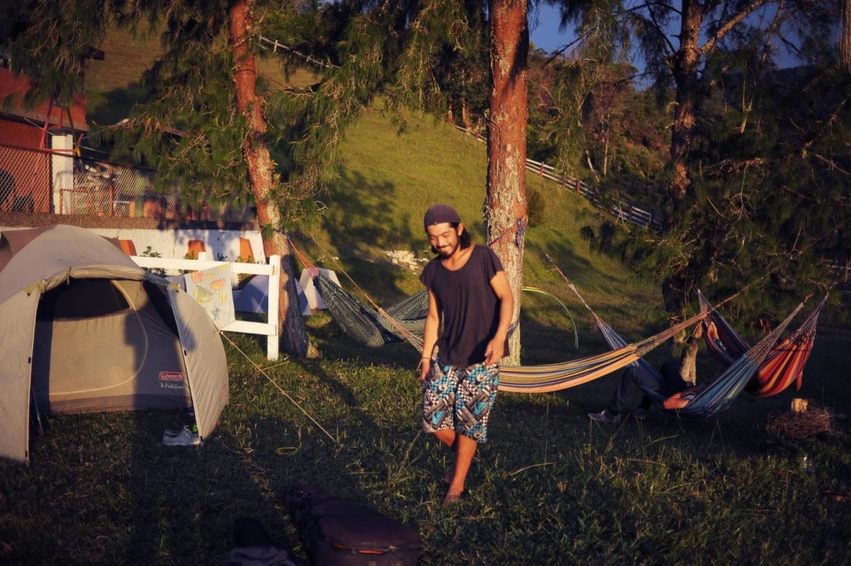 Guy walking on the grass in front of hammocks