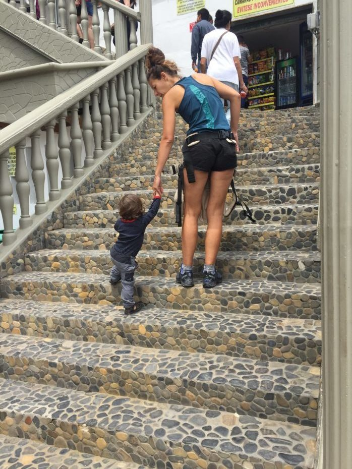 women with child get up stairs of the rock of penol in Guatape